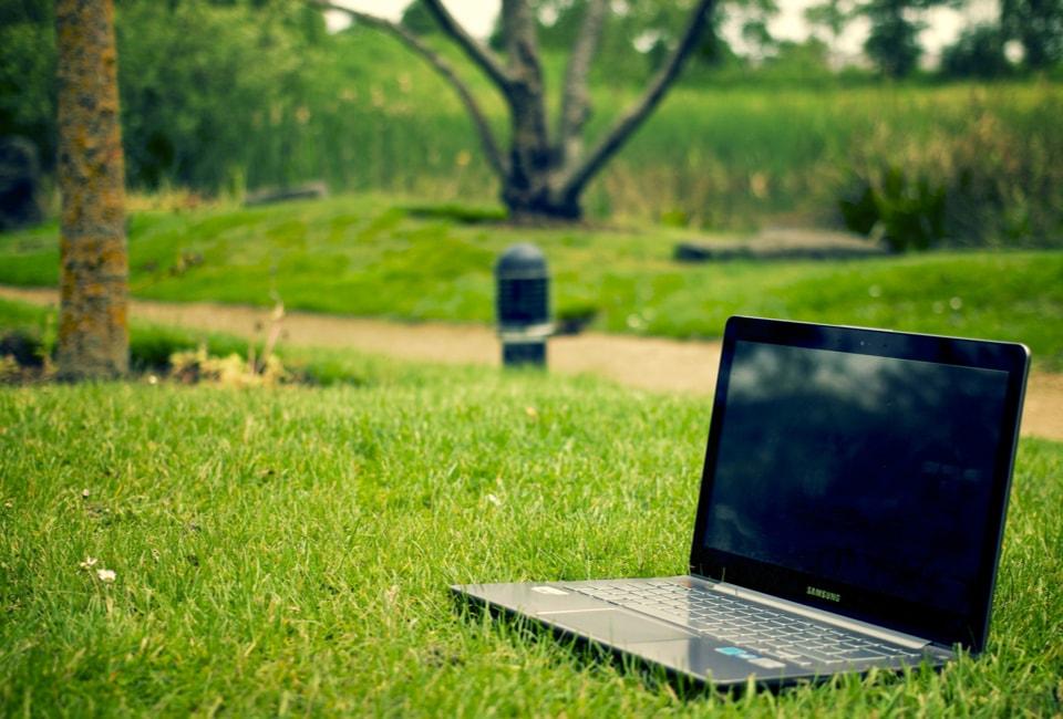 Ordinateur posé dans un parc verdoyant dans une ville écologique et aux bonnes pratiques de recyclage