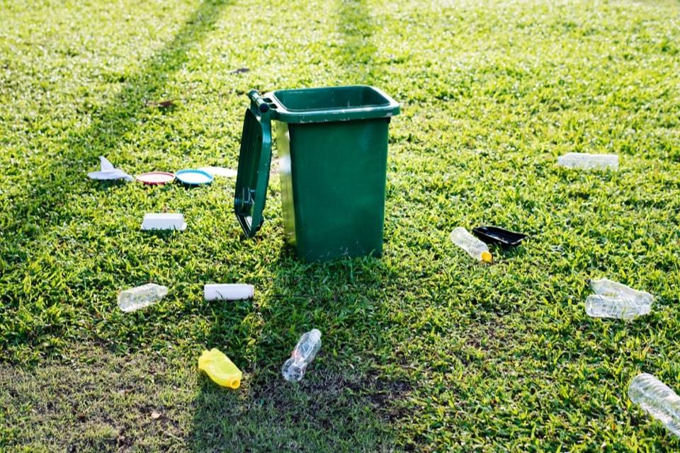 Une poubelle avec des déchets non recyclés autour
